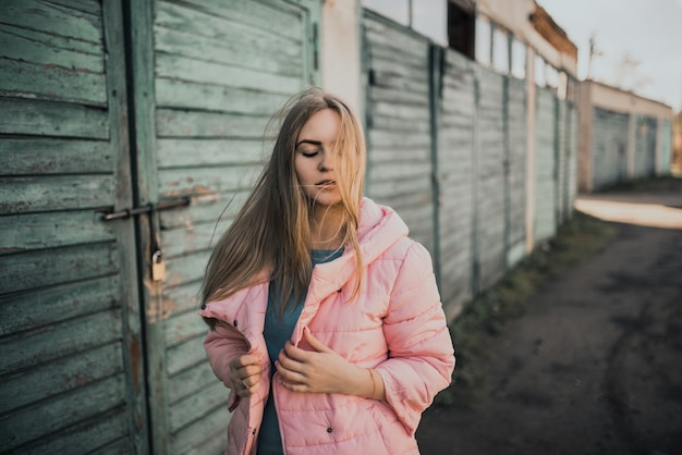 Młoda wspaniała blondynka ubrana moda różowa kurtka i niebieskie dżinsy.