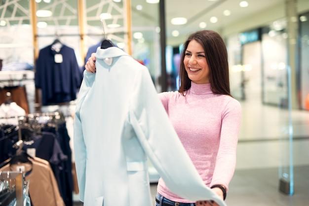 Młoda wspaniała radosna dziewczyna przegląda kobiece bluzki stojąc w sklepie.