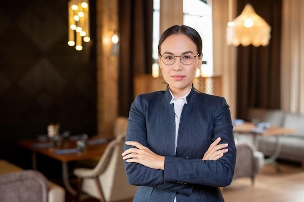 Młoda współczesna kobieta azji w okularach i odzieży wizytowej, patrząc na ciebie wewnątrz restauracji