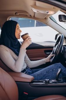 Młoda współczesna muzułmanka pije kawę w samochodzie