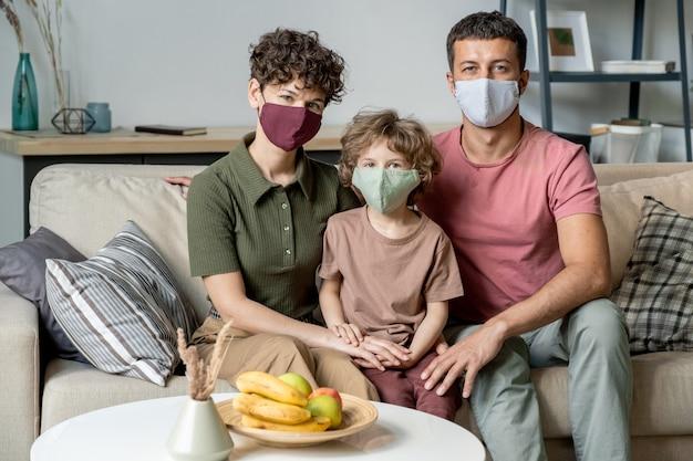 Młoda współczesna para i ich synek w ochronnych maskach siedzą na kanapie w salonie podczas kwarantanny w domu