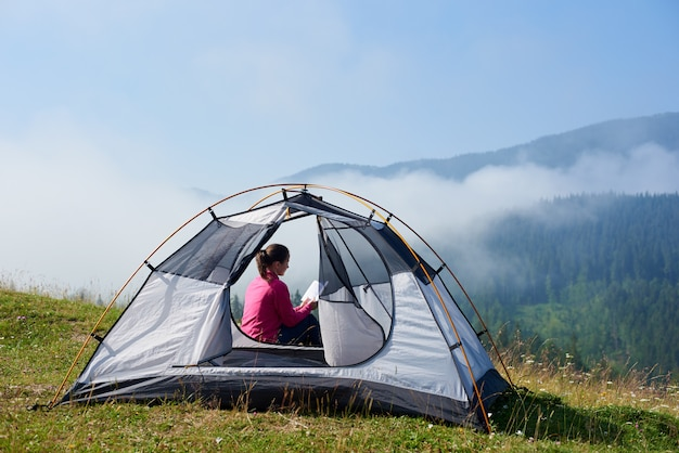 Młoda wycieczkowicz kobieta siedzi przy wejściu do namiotu turystycznego i czyta książkę