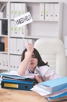 Młoda wyczerpana księgowa lub makler prosząca o pomoc, siedząc przy biurku ze stosami dokumentów finansowych