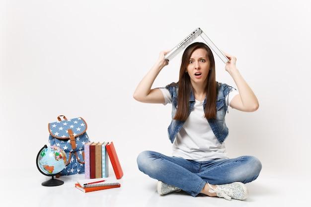 Młoda wyczerpana, oszołomiona studentka trzymająca laptopa nad głową, jak dach, siedzieć w pobliżu globusa, plecaka, podręczników szkolnych na białym tle