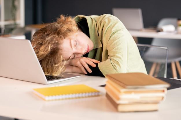Młoda wyczerpana studentka lub kierownik biura, trzymając głowę na rękach podczas drzemki przed laptopem ze stosem książek w pobliżu