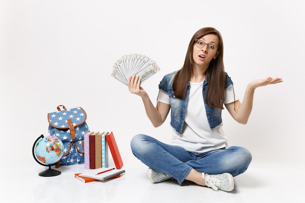 Młoda wyczerpana studentka rozkładająca ręce trzymająca pakiet wiele dolarów, pieniądze w gotówce siedzą w pobliżu globu plecaka szkolne podręczniki na białym tle