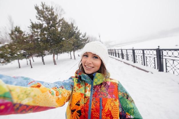 Młoda wysportowana dziewczyna bierze selfie w mroźny i śnieżny dzień. fitness, rekreacja