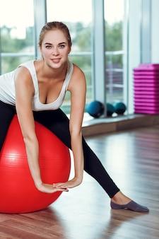 Młoda wysportowana kobieta robi ćwiczenia z piłką fitness w siłowni