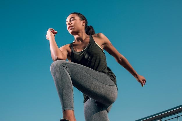 Młoda wysportowana kobieta rozgrzewa się na świeżym powietrzu i przykłada łokieć do kolana