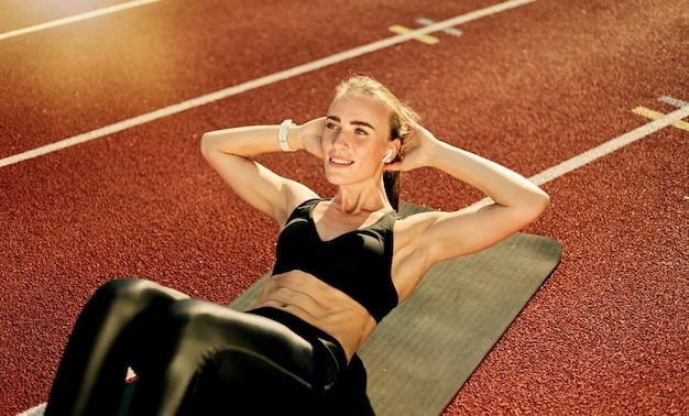 Młoda wysportowana kobieta wykonuje ćwiczenia skręcające na mięśnie brzucha na macie na torze stadionu z czerwoną powłoką w jasny słoneczny dzień
