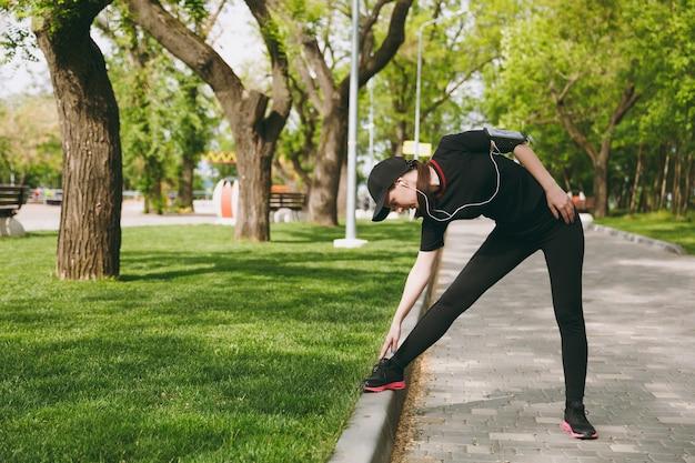 Młoda wysportowana piękna brunetka kobieta w czarnym mundurze i czapce ze słuchawkami robi ćwiczenia rozciągające sportowe, rozgrzewka przed bieganiem w parku miejskim na świeżym powietrzu