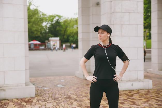 Młoda wysportowana piękna brunetka w czarnym mundurze, czapka ze słuchawkami, ćwiczenia sportowe, rozgrzewka przed bieganiem, słuchanie muzyki w parku miejskim na świeżym powietrzu