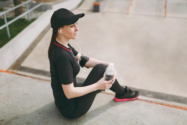 Młoda wysportowana uśmiechnięta kobieta w czarnym mundurze, czapka ze słuchawkami słuchająca muzyki trzymająca butelkę z wodą siedzącą przed lub po bieganiu, trening w parku miejskim na zewnątrz