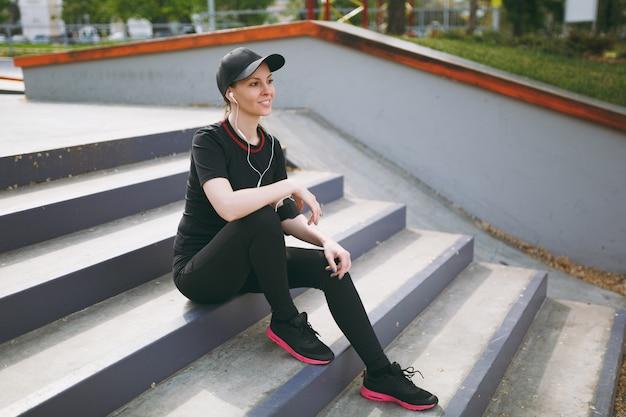 Młoda wysportowana uśmiechnięta kobieta w czarnym mundurze i czapce ze słuchawkami, słuchająca muzyki, odpoczywająca i siedząca przed lub po bieganiu, trenująca na schodach w parku miejskim na zewnątrz