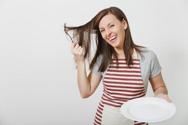 Młoda zabawa szalona brunetka gospodyni w pasiasty fartuch szary t-shirt na białym tle gospodyni kobieta trzyma biały pusty talerz widelec we włosach jak grzebień szczotka do włosów