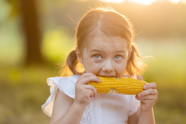 Młoda zabawna dziewczyna je gotowaną kukurydzę dziecko w ogrodzie dziewczyna je kukurydzę na kolbie żywność wolna od gmo
