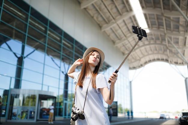 Młoda zabawna ładna podróżniczka turystyczna kobieta z retro aparatem fotograficznym robi selfie na telefonie komórkowym z samolubnym kijem na lotnisku