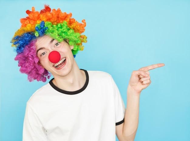 Młoda zabawna męska nastolatka w białej koszulce na niebieskim tle w peruce klauna copyspace