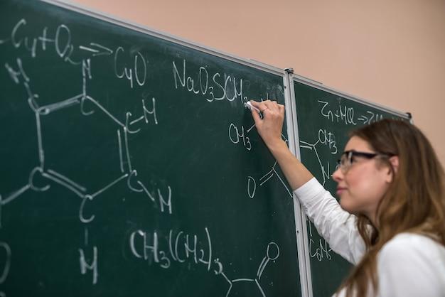 Młoda zabawna nauczycielka w okularach przed kredą tablica z formuł naukowych. chemia
