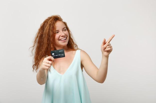 Młoda zabawna ruda kobieta dziewczyna w dorywczo lekkie ubrania pozowanie na białym tle na tle białej ściany. koncepcja życia ludzi. makieta miejsca na kopię. trzymając kartę kredytową, wskazując palcem na bok.