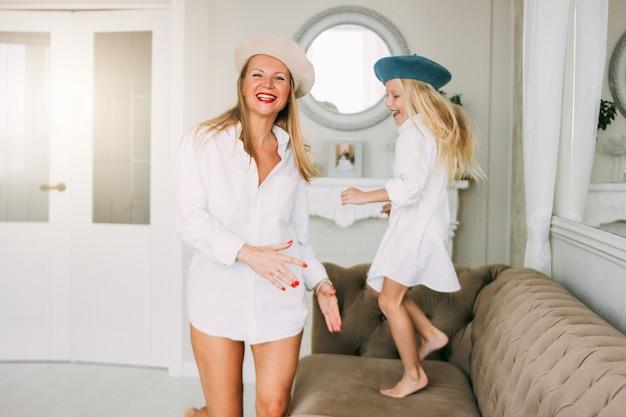 Młoda zabawna szczęśliwa jasnowłosa mama i jej śliczna dziewczyna bawią się razem tańcząc w salonie, szczęśliwy rodzinny styl życia