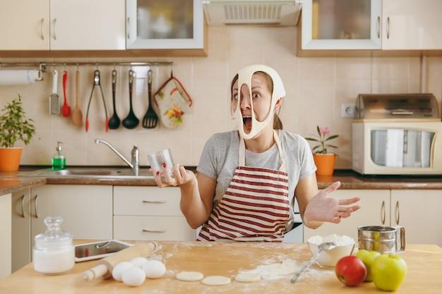 Młoda zabawna wesoła i uśmiechnięta kobieta nakłada ciasto z dziurami na twarzy i bawi się w kuchni. gotowanie w domu. przygotuj jedzenie.