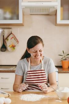 Młoda zabawna wesoła kobieta siedzi przy stole z mąką i idzie przygotować ciasto w kuchni. gotowanie w domu. przygotuj jedzenie.
