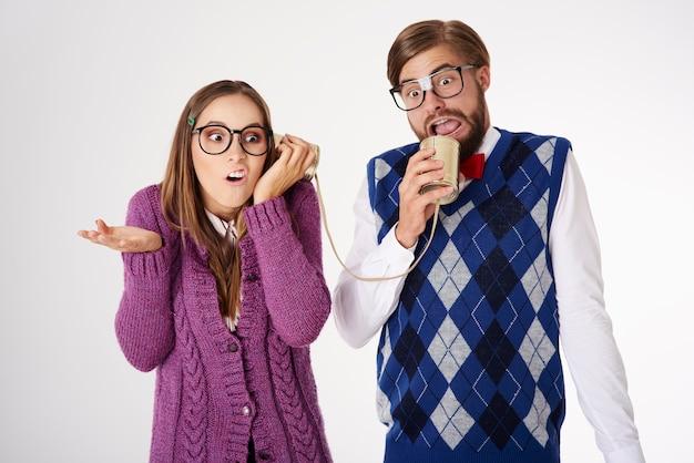 Młoda, zabawnie wyglądająca para maniakiem zabawy na białym tle