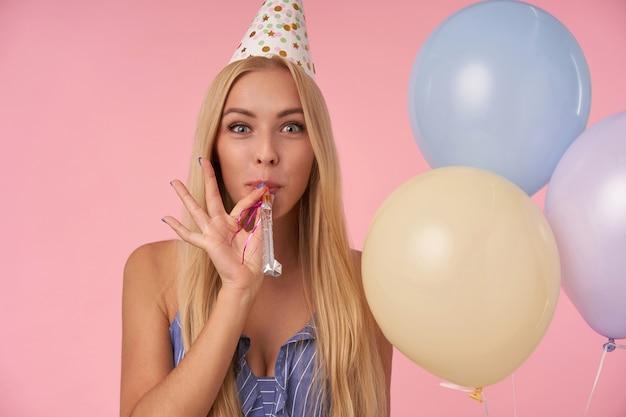 Młoda zachwycona kobieta o długich blond włosach świętuje urodziny z wielobarwnymi balonami, dmucha w róg i szczerze uśmiecha się do kamery. atrybuty ludzi, rozrywki i wakacji