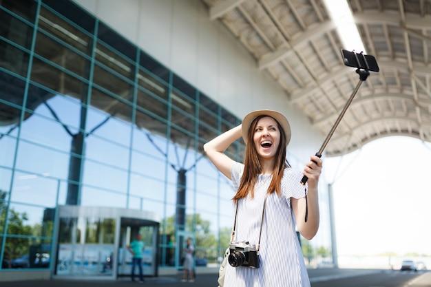 Młoda zachwycona podróżniczka turystyczna kobieta z retro vintage aparatem robi selfie na telefonie komórkowym z monopodem samolubnym kijem na lotnisku