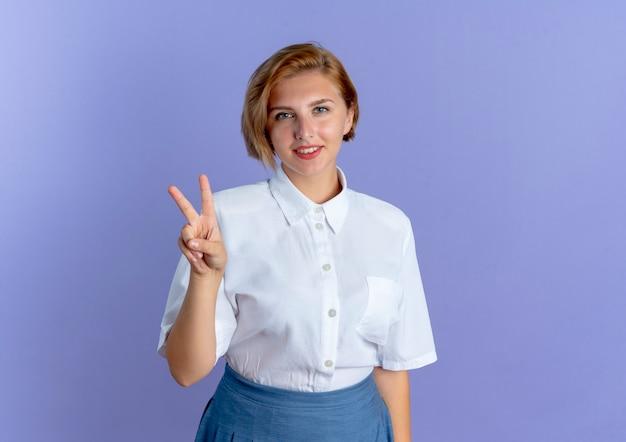 Młoda zadowolona blondynka rosjanka gesty ręką znak zwycięstwa