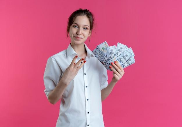 Młoda zadowolona blondynka rosjanka gestykuluje trzy palcami trzymającymi pieniądze na różowo z miejsca na kopię