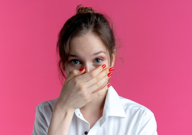 Młoda zadowolona blondynka rosjanka kładzie dłoń na ustach patrząc na kamery