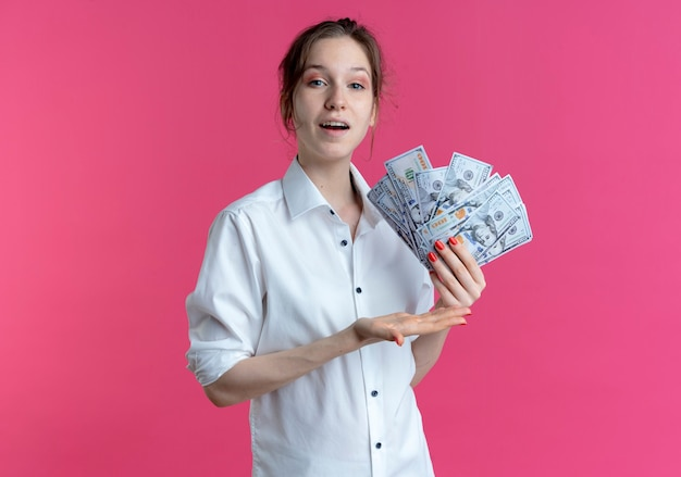 Młoda zadowolona blondynka rosjanka trzyma i wskazuje pieniądze na różowo z miejsca na kopię