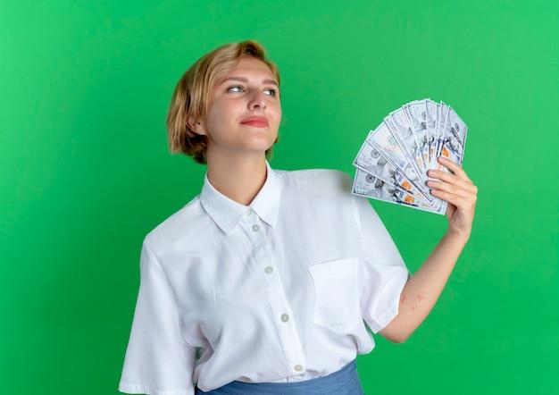Młoda zadowolona blondynka rosjanka trzyma pieniądze patrząc na bok na białym tle na zielonym tle z miejsca na kopię