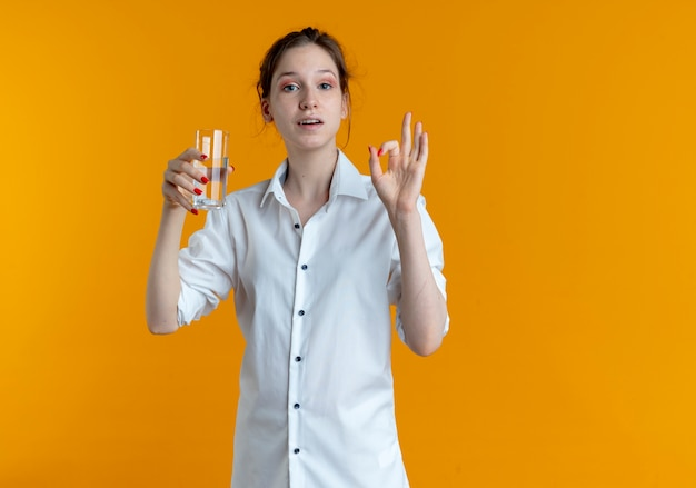 Młoda zadowolona blondynka rosjanka trzyma szklankę wody, wskazując ok ręką znak odizolowany na pomarańczowej przestrzeni z miejsca na kopię