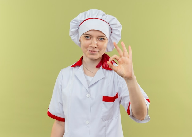 Młoda zadowolona blondynka szef kuchni w mundurze szefa kuchni gestów ok ręka znak na białym tle na zielonej ścianie