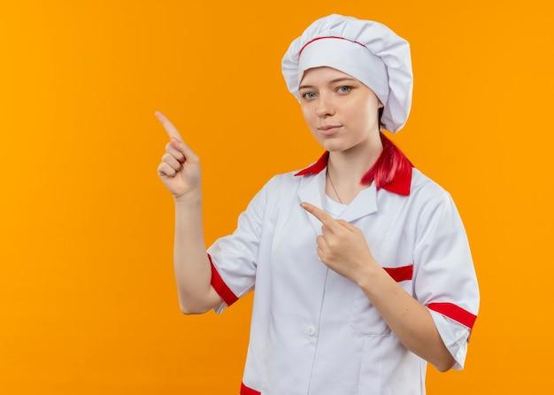 Młoda zadowolona blondynka szef kuchni w mundurze szefa kuchni wskazuje na bok na białym tle na pomarańczowej ścianie