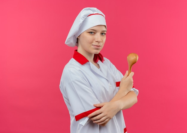 Młoda zadowolona blondynka szefa kuchni w mundurze szefa kuchni stoi bokiem ze skrzyżowanymi rękami i trzyma drewnianą łyżkę na białym tle na różowej ścianie