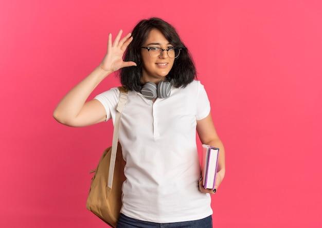 Młoda zadowolona całkiem kaukaska uczennica w okularach z plecami i słuchawkami na szyi trzyma książkę i notatnik z podniesioną ręką na różowo z miejsca na kopię