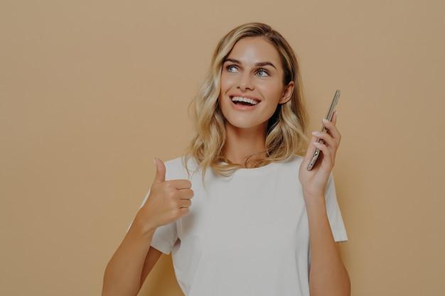 Młoda zadowolona dziewczyna w zwykłych ubraniach trzymająca telefon komórkowy i pokazująca kciuk w górę gestem jest exci