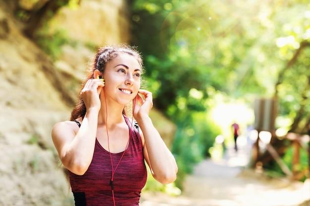Młoda zadowolona kobieta w stroju sportowym w parku podczas ćwiczeń na ulicy słucha muzyki na słuchawkach