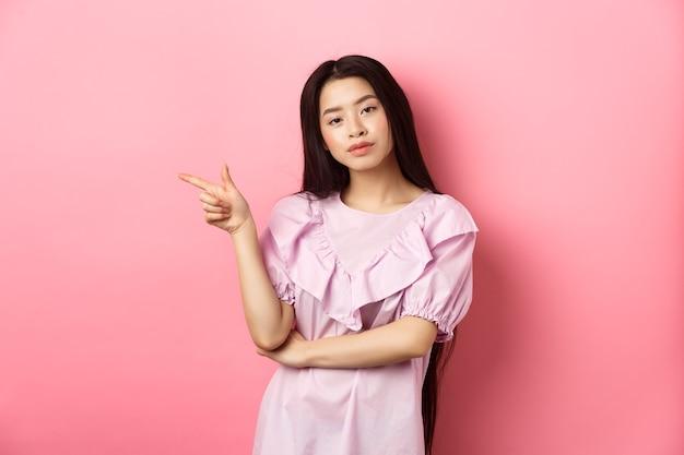 Młoda zadowolona z siebie azjatka wyglądająca fajnie i wskazująca palcem w lewo na logo, reklamujący produkt na różowym romantycznym tle.