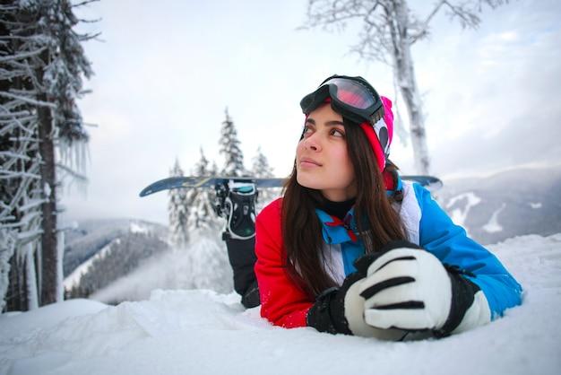 Młoda zadumana kobieta w zimie w śnieżnym lesie na górze gór