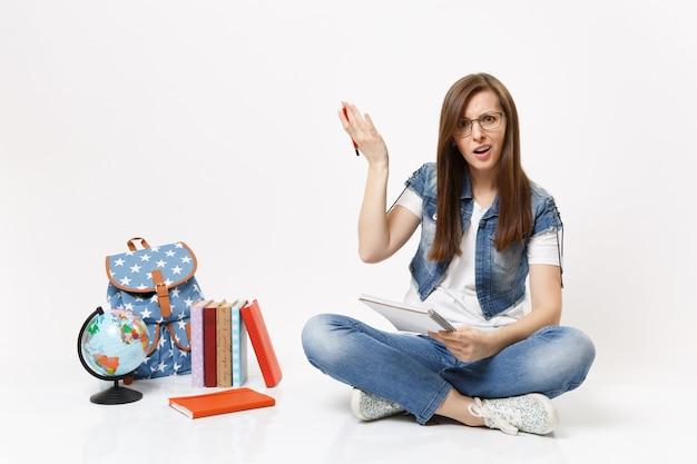 Młoda zakłopotana studentka w okularach rozkładająca ręce, trzymająca ołówek i notatnik, siedząca w pobliżu globu plecaka na białym tle