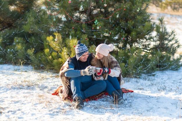 Młoda zakochana para pije gorący napój z piankami, siedząc zimą w lesie, schowana w ciepłych, wygodnych dywanikach i ciesząc się przyrodą. rozmawiają i śmieją się z kubka gorącego napoju w lesie