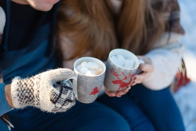 Młoda zakochana para pije gorący napój z piankami, siedząc zimą w lesie, schowana w ciepłych, wygodnych dywanikach i ciesząc się przyrodą