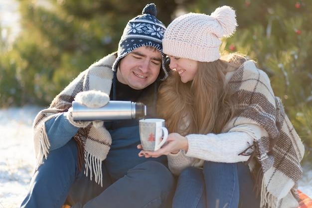 Młoda zakochana para pije gorący napój z termosu, siedząc zimą w lesie, schowana w ciepłe, wygodne dywany i ciesząc się przyrodą. facet nalewa drinka z termosu w filiżance
