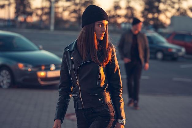 Młoda zakochana para podchodzi do miasta. wiosna jesień. facet ma na sobie kurtkę i kapelusz. dziewczyna w kapeluszu i skórzanej kurtce z szalikiem