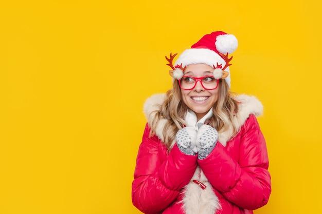 Młoda zamarznięta blondynka w świątecznej czapce mikołaja i czerwonej kurtce, odwracająca wzrok na puste miejsce na kopię